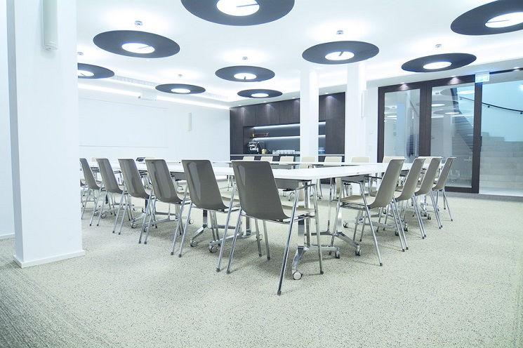 Heller Besprechungsraum mit Tischen in U-Form